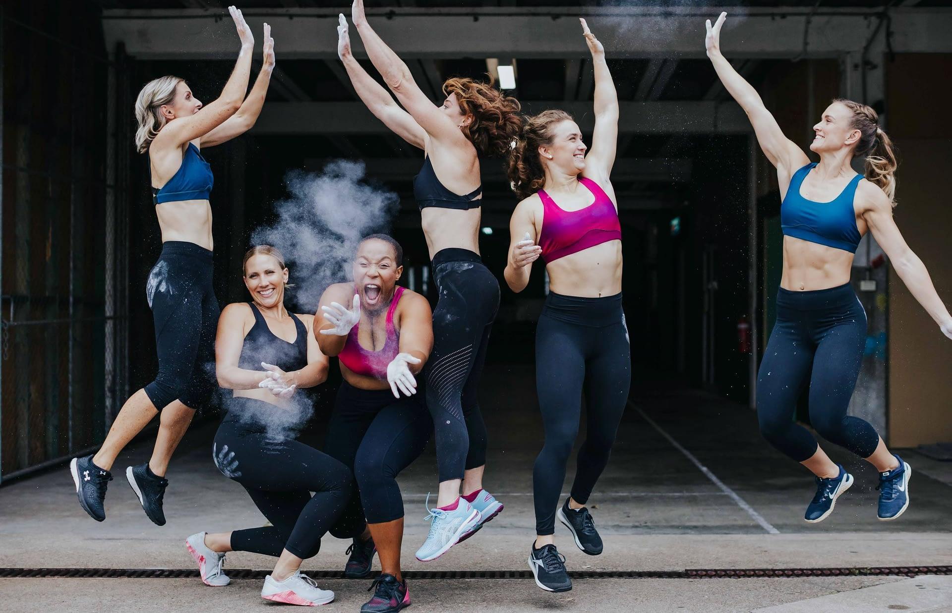 women in sports bras high fiving