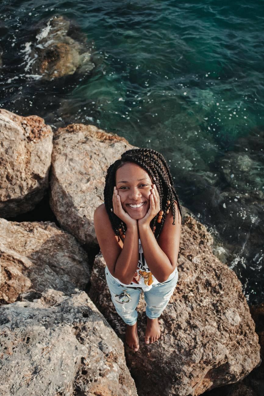 happy black tourist on boulder near sea