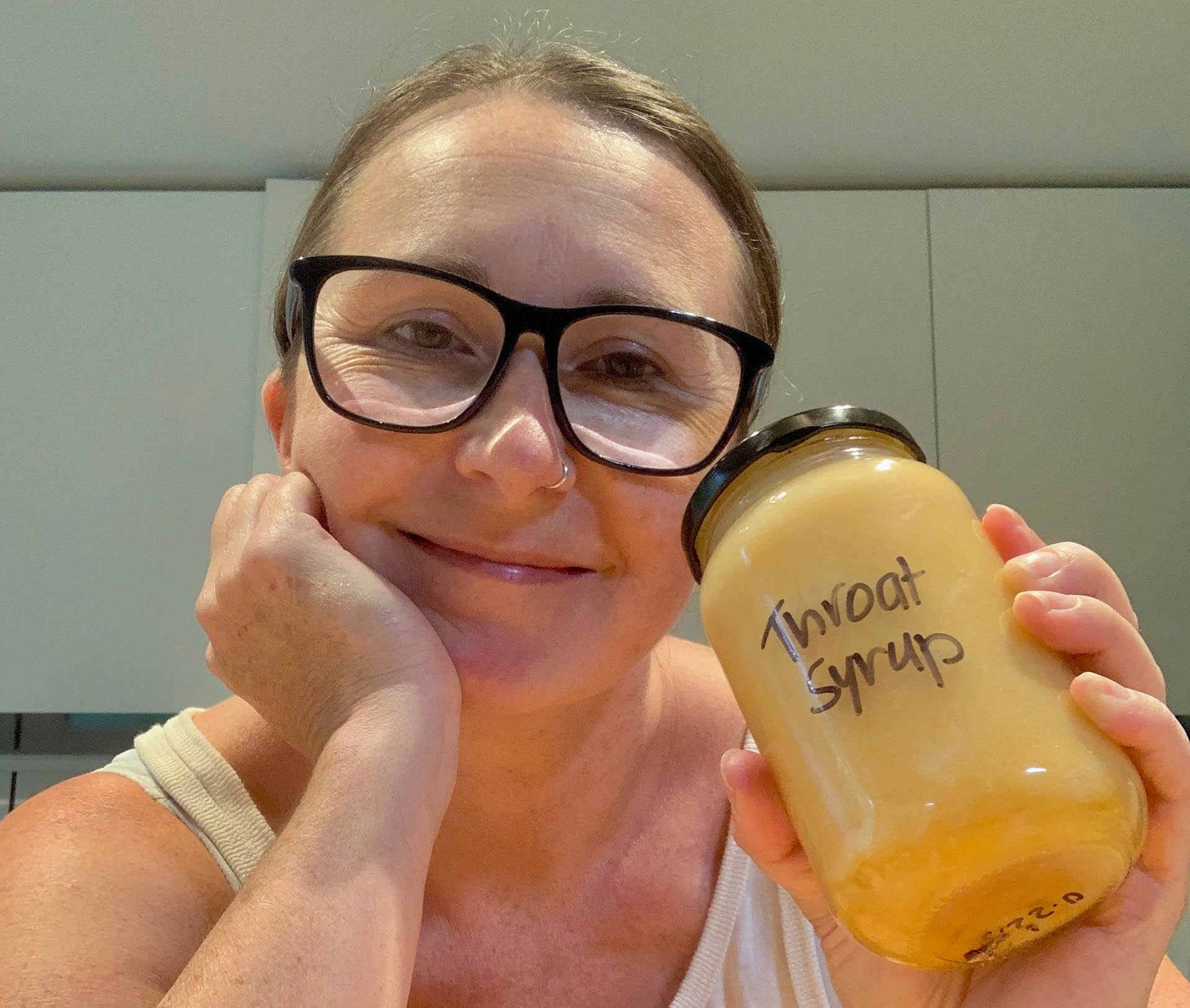 woman holds jar of homemade throat syrup