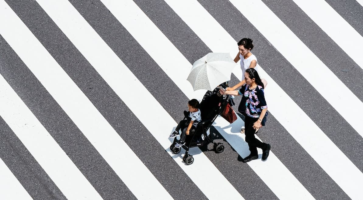 aerial view of a family walking across black and white diagonal lines on the ground
